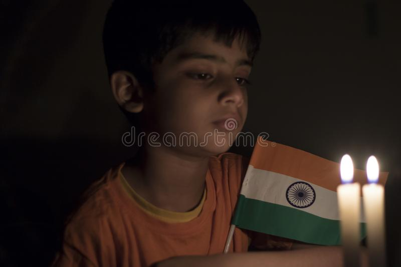 A child in thoughtful moment with Indian National flag. A cute child in a thoughtful moment sitting with Indian national flag before Independence day celebration royalty free stock photos