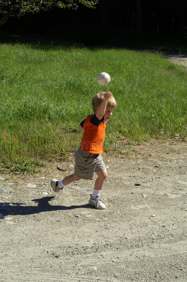 Child throwing a ball stock photo
