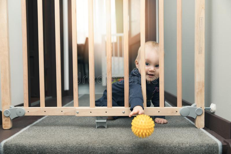 child throwing ball away through safety gates in front of stairs royalty free stock photo