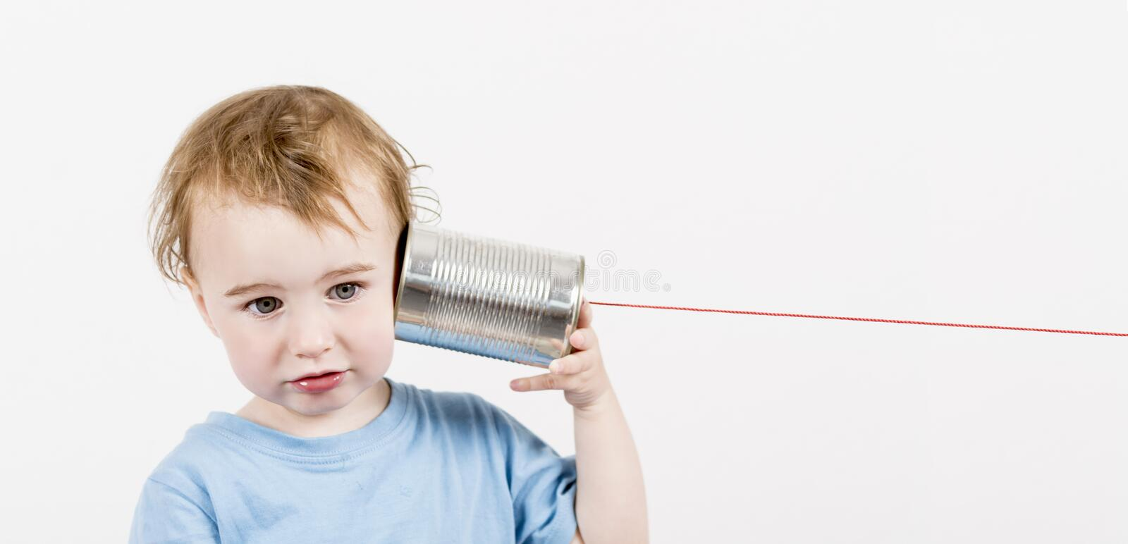 Child with tin can phone. Young, disappointed child listening to tin can phone. caucasian child in horizontal image royalty free stock photo