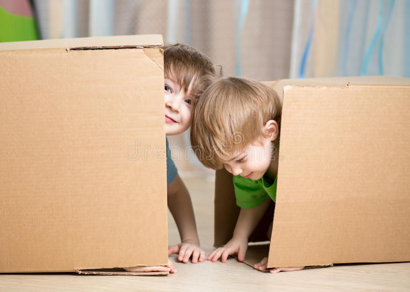 Child and toddler boys playing in cardboard boxes stock photo