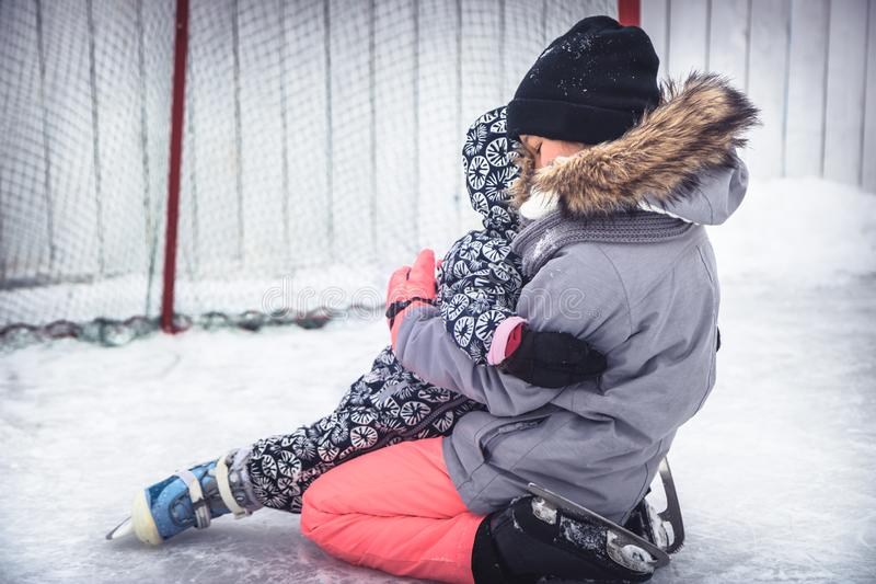 Child toddler fall in elder sisters embrace when learning ice skating on skating rink overcoming difficulties through injuries  in. A snow park during winter royalty free stock photography