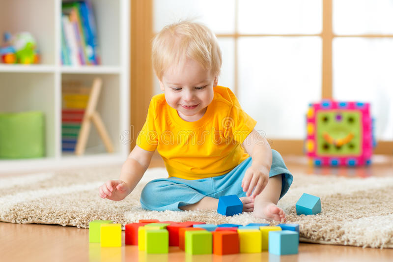 Child toddler playing toy blocks in his room or nursery stock photos