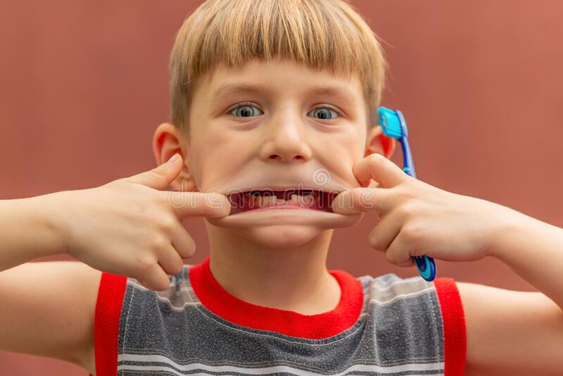 A child with a toothbrush in his hand shows a toothless mouth swelling his cheeks stock photo