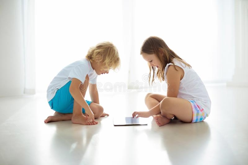 Child with tablet computer. PC for kids. Child with touch screen tablet pc. Kid playing computer game. Little girl and boy in white bedroom reading on digital stock image