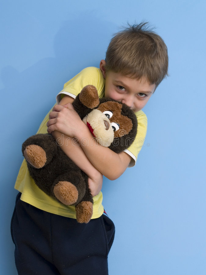 Child with toy. Boy hugging a monkey on blue background royalty free stock photo