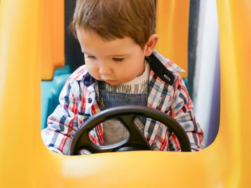 Child on a toy car. The car is yellow. child 0-1 year old.  royalty free stock photos
