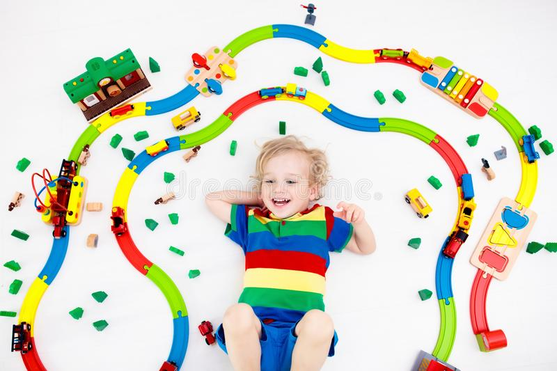 Child with toy train. Kids wooden railway. Kids play with toy train railway. Child playing with colorful rainbow wooden trains. Toys for little boy. Preschooler stock images