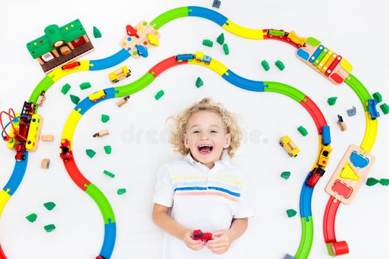 Child with toy train. Kids wooden railway. Kids play with toy train railway. Child playing with colorful rainbow wooden trains. Toys for little boy. Preschooler stock photos