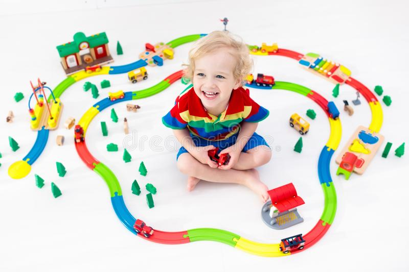 Child with toy train. Kids wooden railway. Kids play with toy train railway. Child playing with colorful rainbow wooden trains. Toys for little boy. Preschooler royalty free stock photography