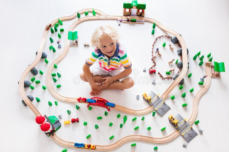 Child with toy train. Kids wooden railway. Kids play with toy train railway. Child playing with wooden trains. Toys for little boy. Preschooler building rail royalty free stock photo
