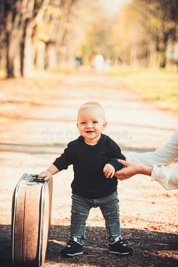 Child travel for vacation with bag with mothers hand. Small boy carry retro suitcase on natural landscape. Kid traveler. With luggage outdoor. Vacation stock photography