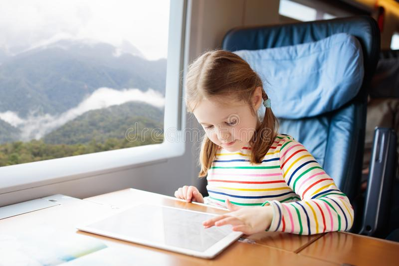 Kids travel by train. Railway trip with child. Child traveling by train. Little kid in a high speed express train on family vacation in Europe. Travel by royalty free stock photography
