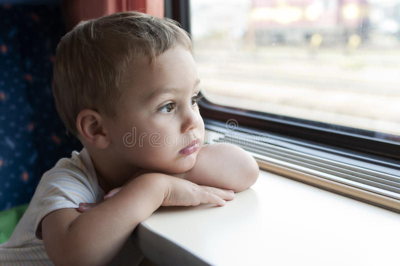 Child travelling by train. Child travelling on train looking through the window royalty free stock images