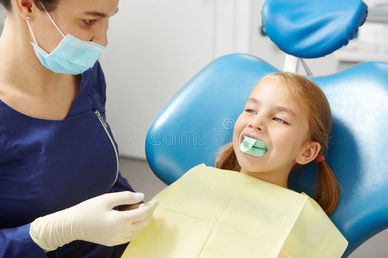 Child tries on a mouthpiece to correct the bite in the dentist`s office in pediatric dentistry. Early prevention, raising awareness, oral hygiene demonstration royalty free stock photo