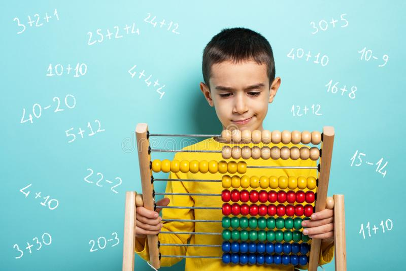 Child tries to solve mathematical problem with abacus. Cyan background royalty free stock image