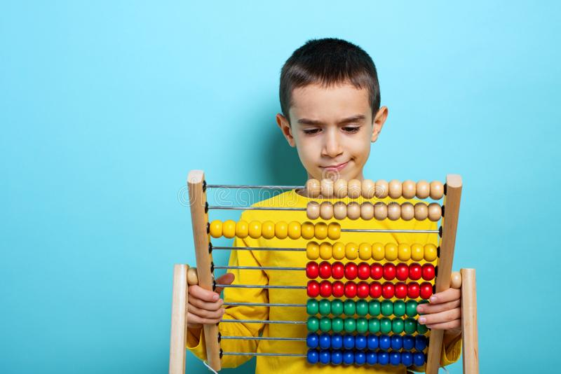 Child tries to solve mathematical problem with abacus. Cyan background stock photo