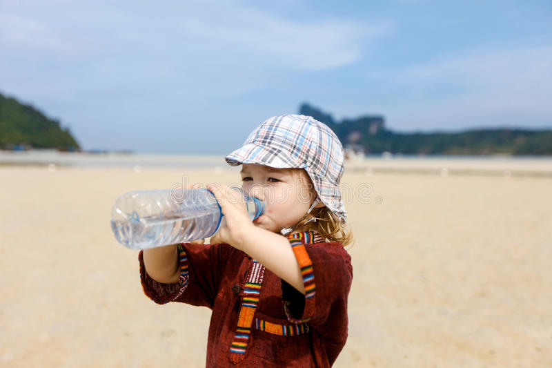 Child on tropical beach, drinking bottled water. Child on a trip to a sandy tropical beach in summer, drinking bottled water with soluble electrolytes for stock images