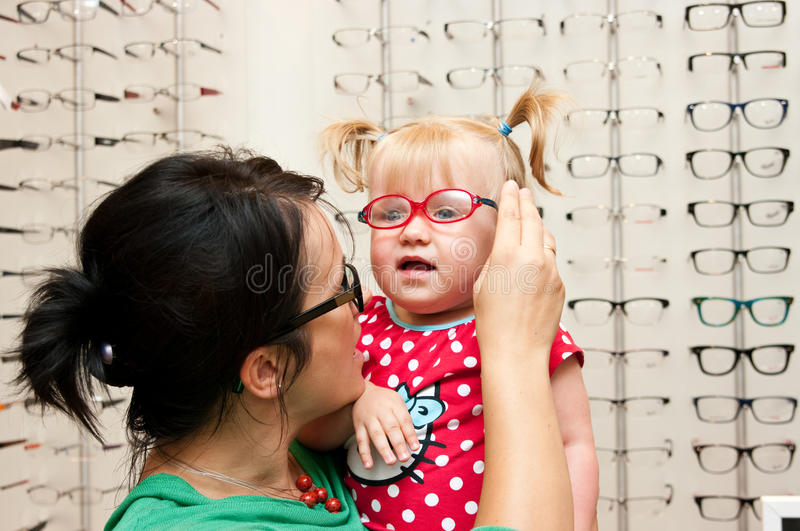 Child trying on eyeglasses. A cute child trying on eyeglasses in an optician shop, together with the mother or shop assistant stock photography