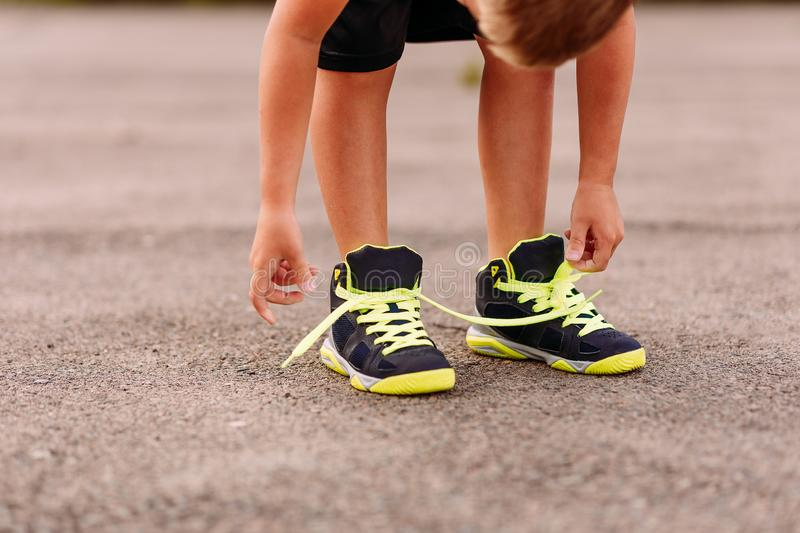 Child tying shoelaces on sports shoes in summer. Outdoors stock photo