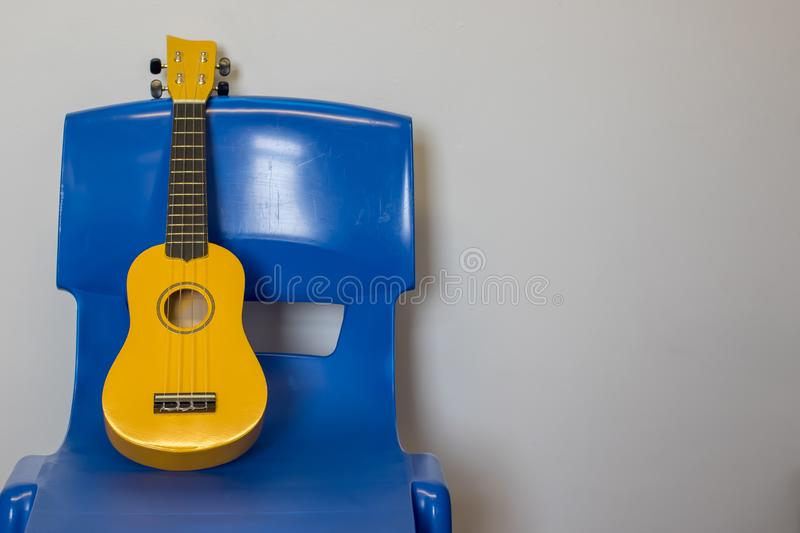 Child ukulele on chair. School music lesson practice room royalty free stock photo