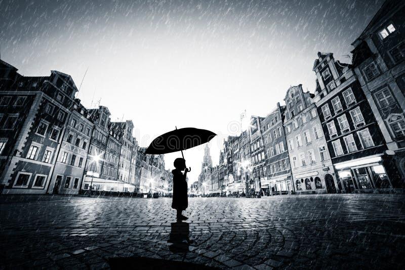 Child with umbrella standing alone on cobblestone old town in rain stock image