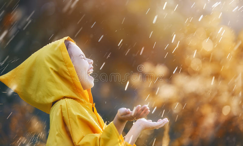 Child under autumn rain. Happy funny child under the autumn shower. Girl is wearing yellow raincoat and enjoying rainfall royalty free stock photography
