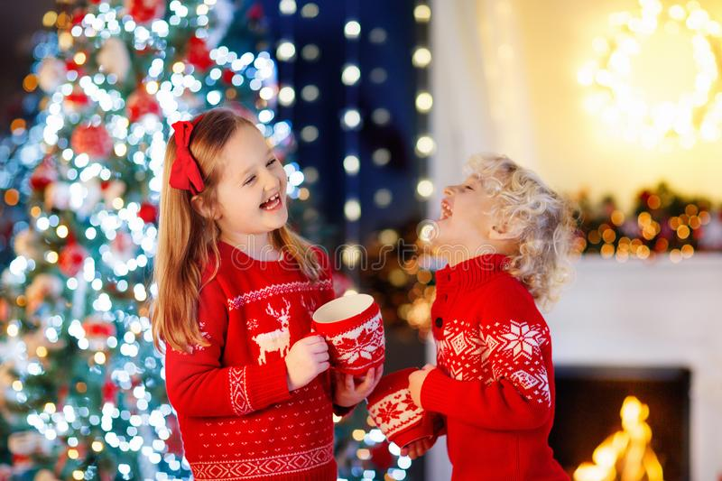 Child under Christmas tree at home. Little boy and girl in knitted sweater with Xmas ornament drink hot chocolate. Family with stock photo
