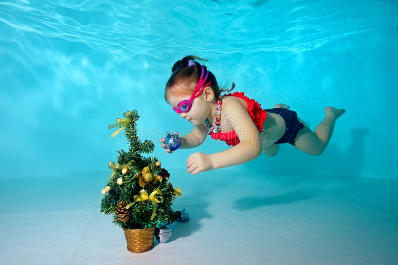 Child underwater in the pool decorates the Christmas tree with Christmas toys. Portrait. Shooting under water. Horizontal orientat stock image