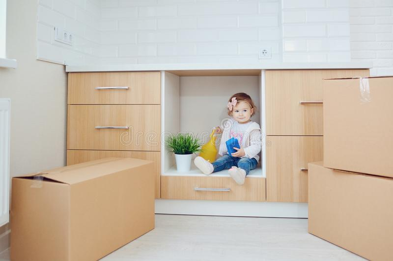 The child unpacks the boxes in the new house stock photos