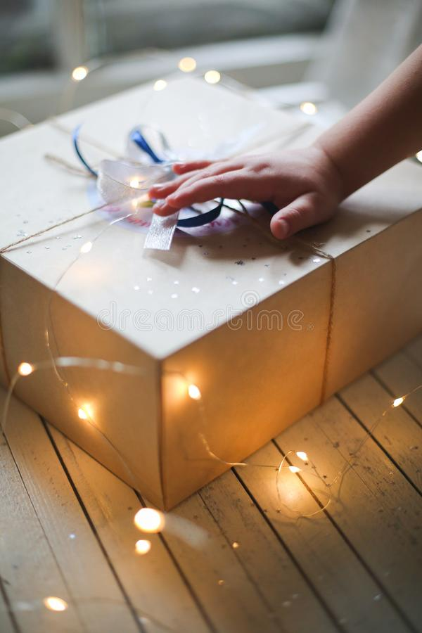 Child unties the box with a gift royalty free stock photo