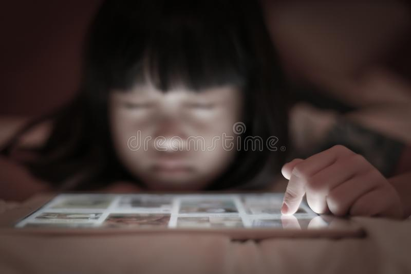 Child uses tablet internet online with scare emotion. stock images