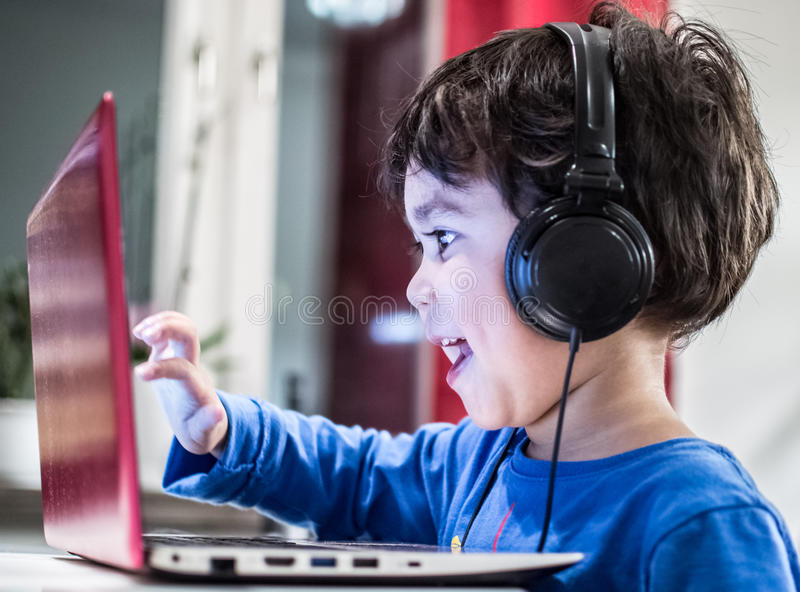 Child using computer. An enthusiastic young boy wearing headphones and interacting with a laptop