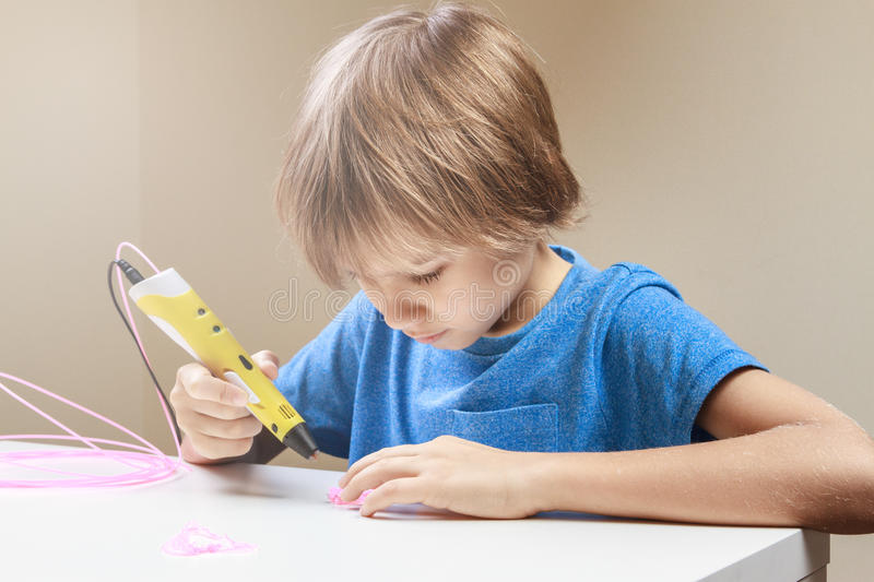 Child using 3D printing pen. Boy making new item. Creative, technology, leisure, education concept stock photography