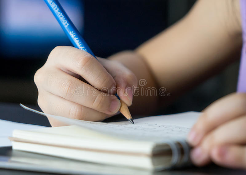Child is using pencil to practice writing on a book. royalty free stock photo