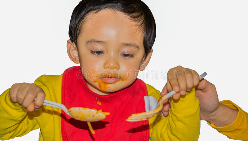 Child using plastic spoon and fork royalty free stock photography