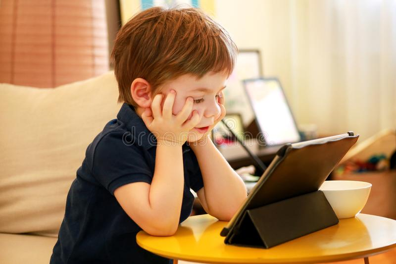 Child using tablet pc on bed at home. Cute boy on sofa is watching cartoon, playing games and learning from laptop. Education, fun stock image