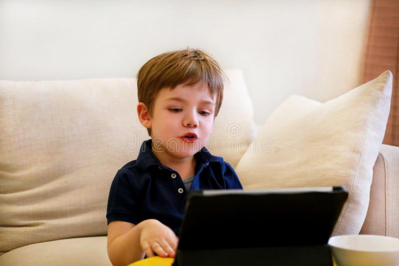 Child using tablet pc on bed at home. Cute boy on sofa is watching cartoon, playing games and learning from laptop. Education, fun stock photo