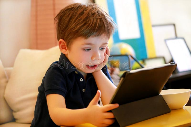 Child using tablet pc on bed at home. Cute boy on sofa is watching cartoon, playing games and learning from laptop. Education, fun stock images