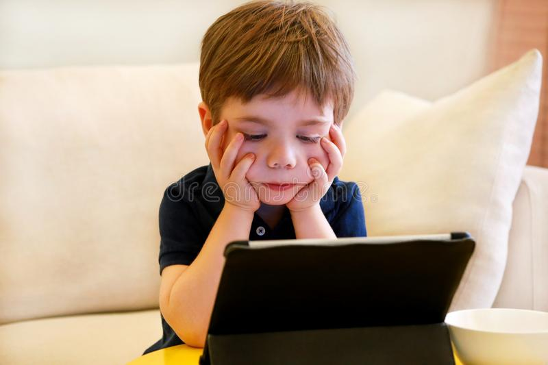 Child using tablet pc on bed at home. Cute boy on sofa is watching cartoon, playing games and learning from laptop. Education, fun stock photography