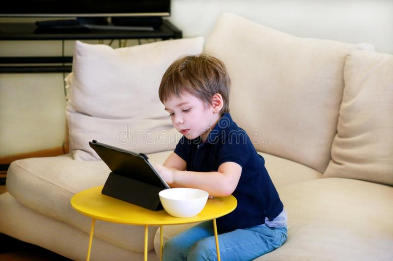 Child using tablet pc on bed at home. Cute boy on sofa is watching cartoon, playing games and learning from laptop. Education, fun royalty free stock photography