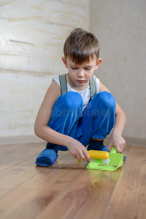 Child using toy broom and dustpan royalty free stock image