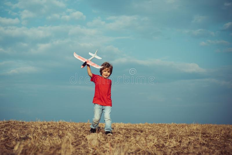 Child in the village with plane in his hands. Retro style airplane on nature background. Child boy toddler playing with stock images