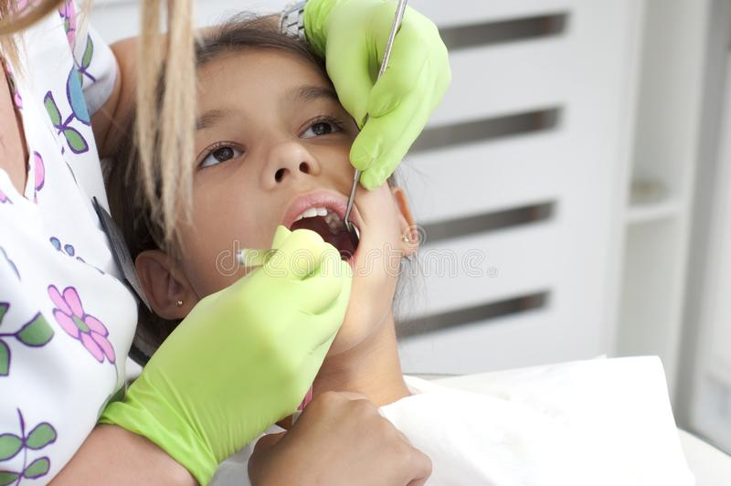 Child visits the dentist, sitting in his chair and opened her mo. Uth for examination of the teeth stock photo