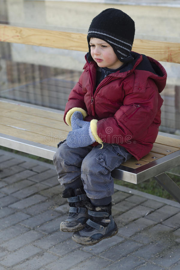 Child waiting at bus stop. Poor child waiting at bus stop in cold winter weather stock images