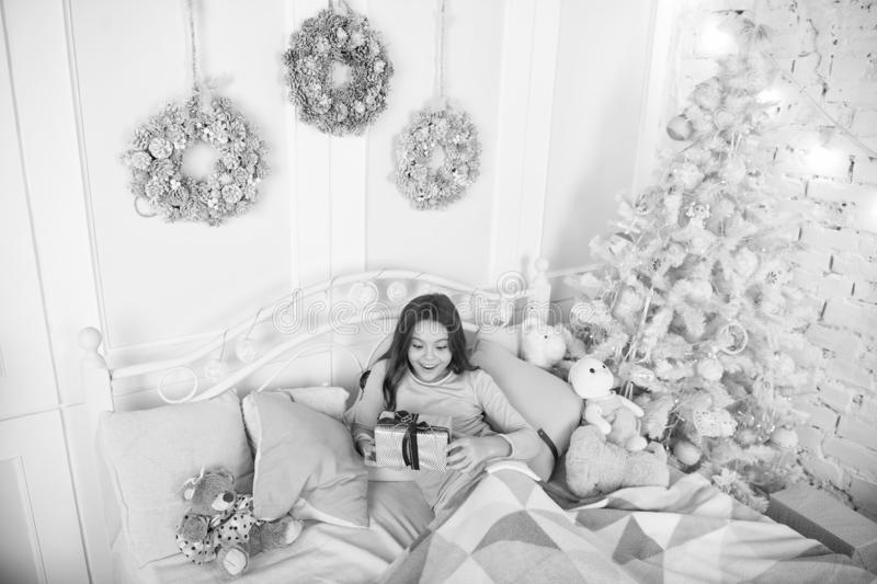 Child waiting christmas in bedroom. Kid lay in bed relaxing. Home is the best place in the world. Girl little kid. Relaxing on bed light interior with christmas stock image