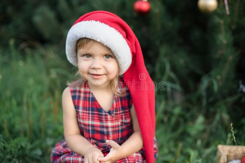 Child waiting for a Christmas in wood in juli. portrait of little children near christmas tree. girl decorating christmas tree royalty free stock photo