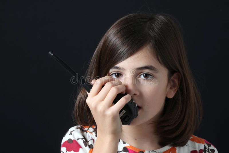 Child with walkie-talkie. On black background stock photo