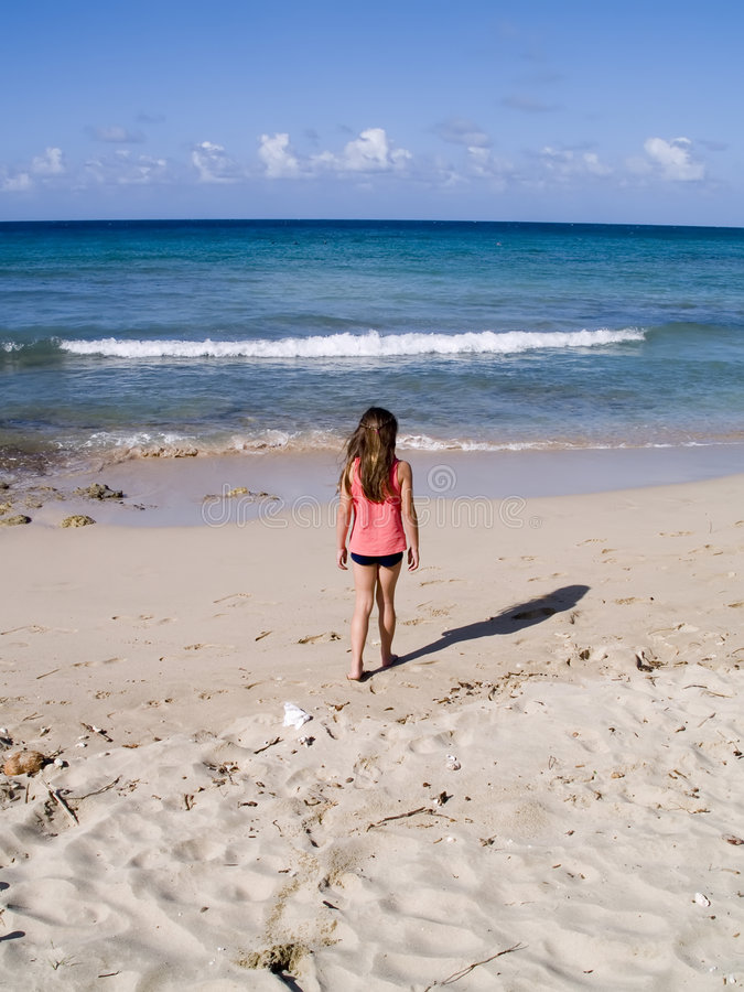 Child walking along beach stock photography