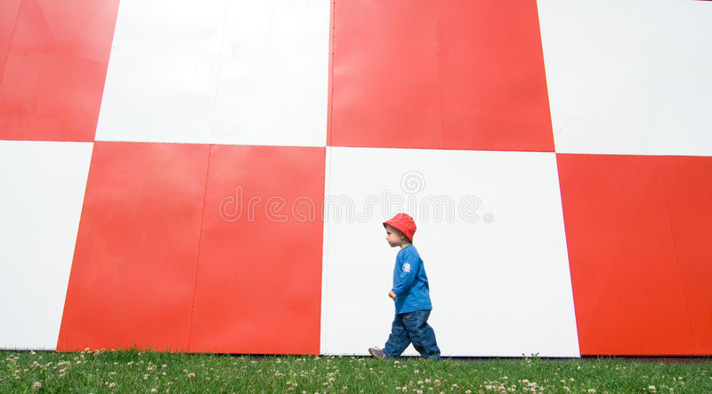 Child Walking by Checked Wall royalty free stock photo